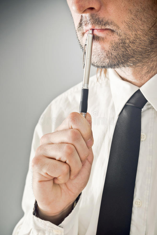 Affärsman som tänker med blyertspennan i hans mun royaltyfri bild