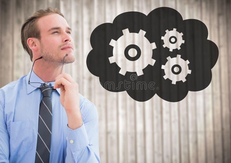 Affärsman som tänker mot oskarp wood panel och molnet med kugghjuldiagrammet royaltyfri bild