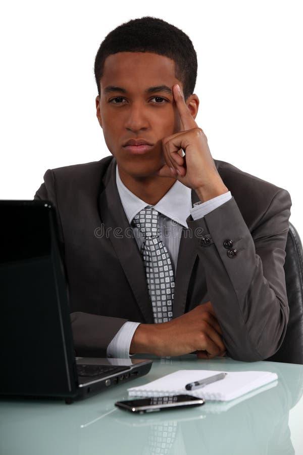 Affärsman som tänker på hans skrivbord arkivbilder