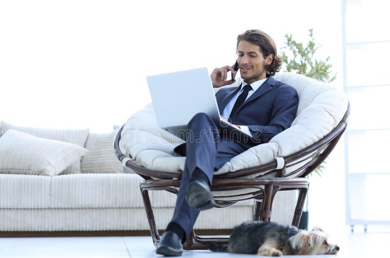 Affärsman som talar på ett smartphonesammanträde i vardagsrummet arkivbilder