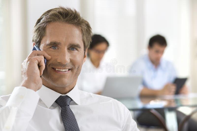 Affärsman som talar på mobiltelefonen medan i ett möte fotografering för bildbyråer