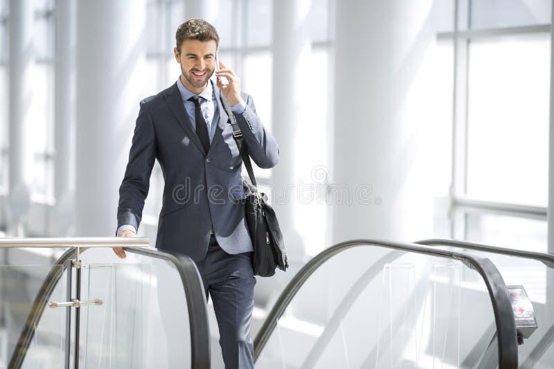 Affärsman som talar på mobiltelefonen medan på rulltrappan royaltyfri fotografi