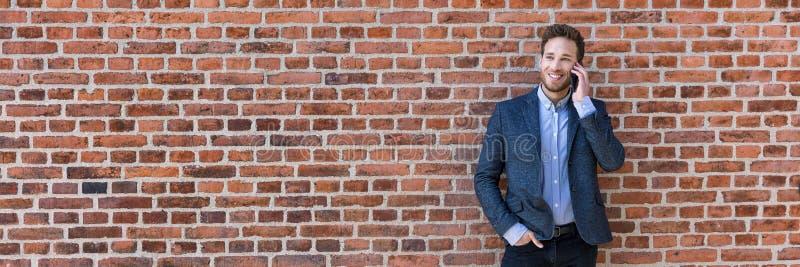 Affärsman som talar på panorama- baner för mobiltelefon av textur för bakgrund för tegelstenvägg Lycklig ung affärsman som in anv arkivbilder