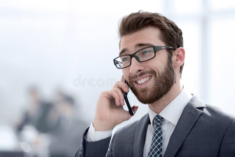 Affärsman som talar på smartphonen på kontorsbakgrund royaltyfri bild