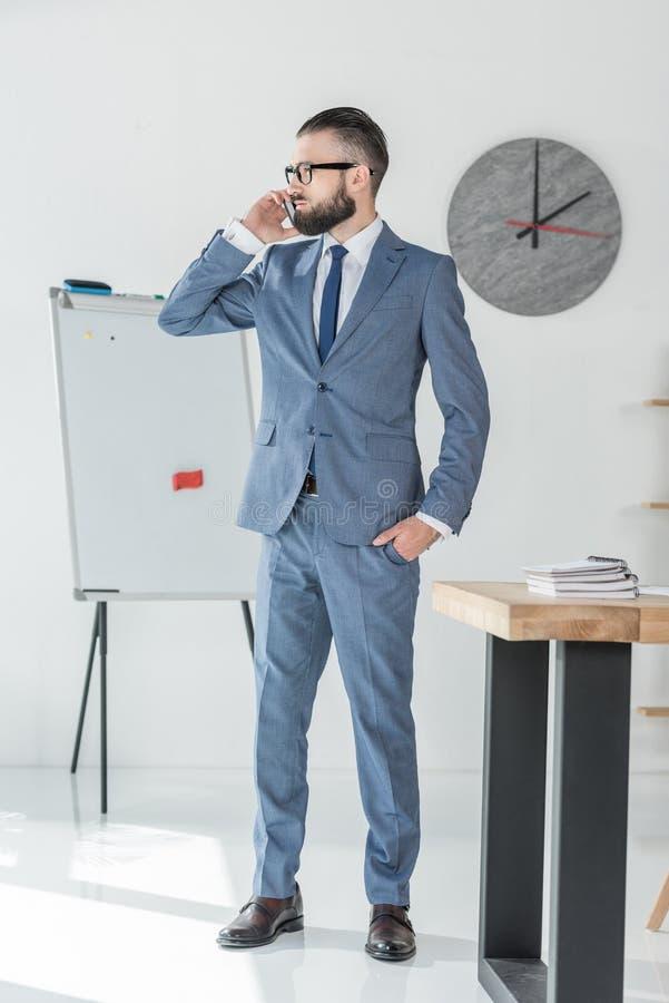 Affärsman som talar på smartphonen, medan stå på arbetsplatsen i regeringsställning fotografering för bildbyråer