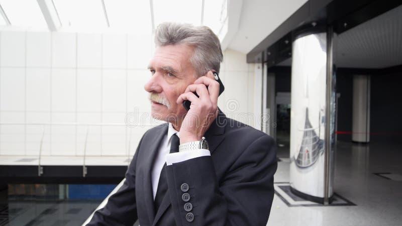 Affärsman som talar på telefonen i byggnadshall royaltyfri bild