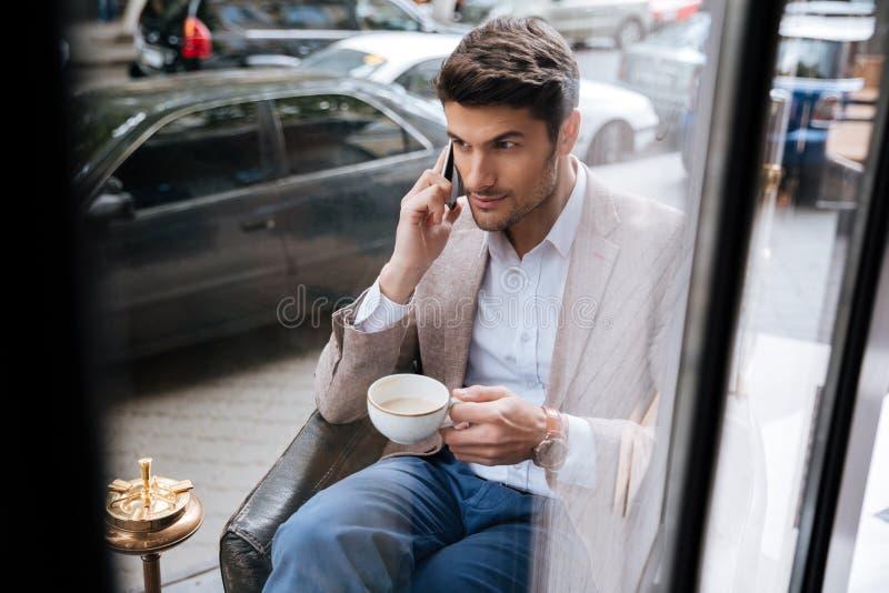 Affärsman som talar på telefonen i en coffee shop royaltyfri bild