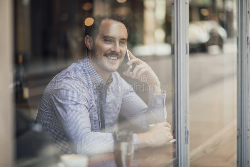Affärsman som talar på telefonen i kafé arkivbilder
