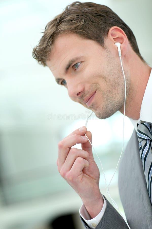 Affärsman som talar på telefonen med hörlurar arkivfoto