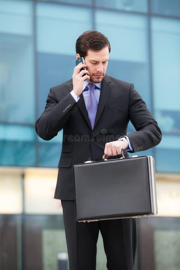 Download Affärsman Som Talar På Telefonen Och Ser Klockan Fotografering för Bildbyråer - Bild av entreprenör, affärsman: 37346185