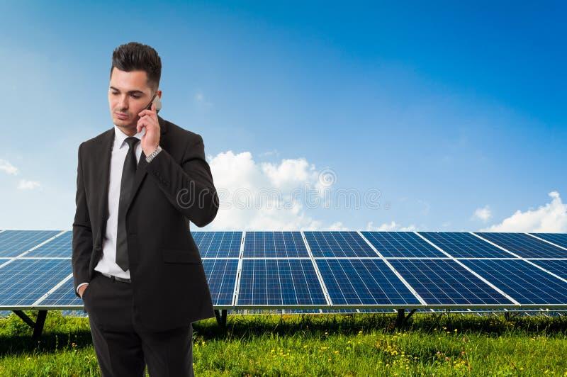 Affärsman som talar på telefonen på backgroun för solenergipaneler royaltyfri fotografi