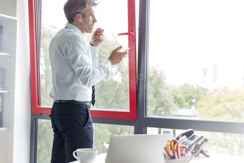 Affärsman som talar till och med hörlurar med smartphonen på kontoret fotografering för bildbyråer