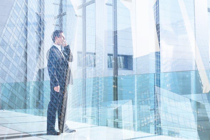 Affärsman som talar vid mobiltelefonen i det kontors-, kommunikations- eller framgångbegreppet royaltyfria bilder