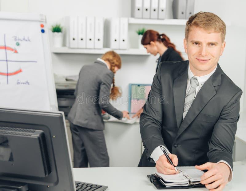 Affärsman som tar anmärkningar och leenden arkivfoto