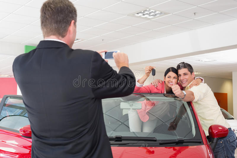 Affärsman som tar bilden av paren i deras nya bil arkivfoton