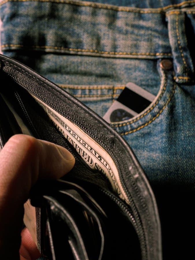 Affärsman som tar pengar ut ur hans plånbok, grund DoF royaltyfri bild