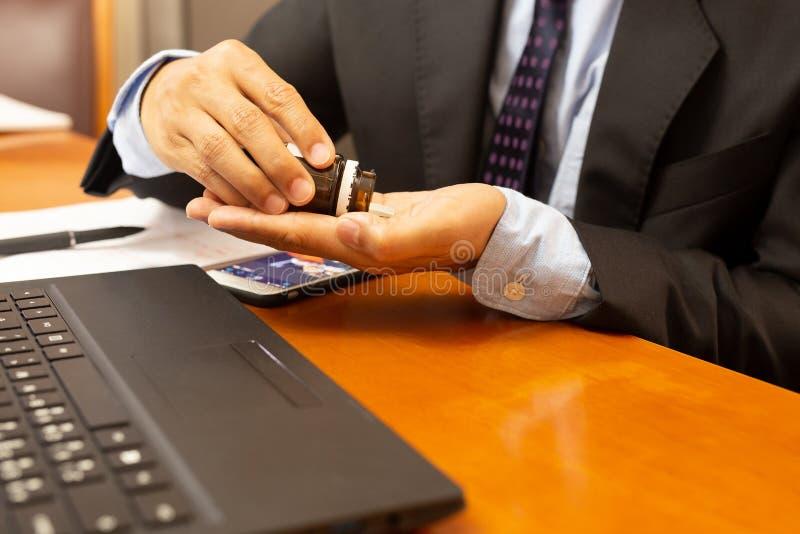 Affärsman som tar smärtstillande medelpillret med bärbara datorn på trätabellen royaltyfria bilder