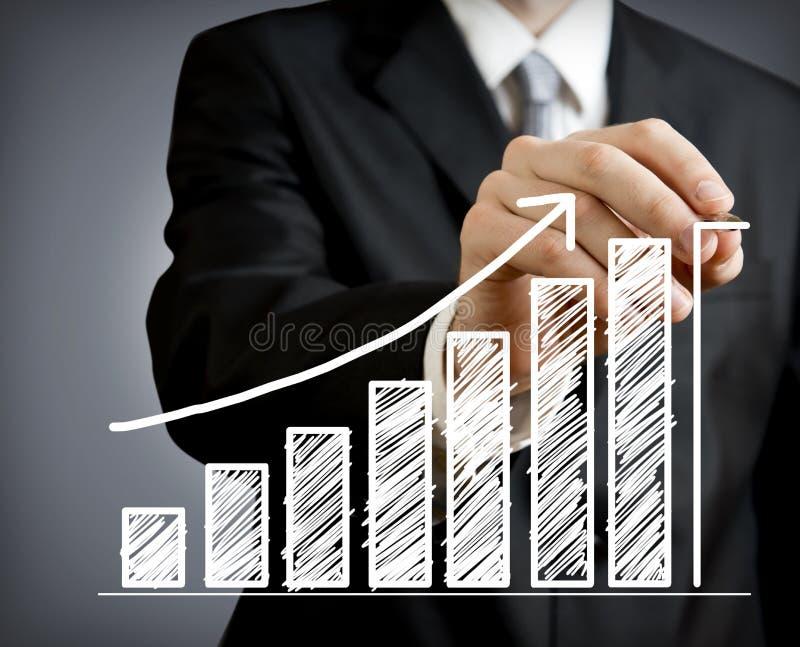 Affärsman som tecknar en växande graf royaltyfri bild