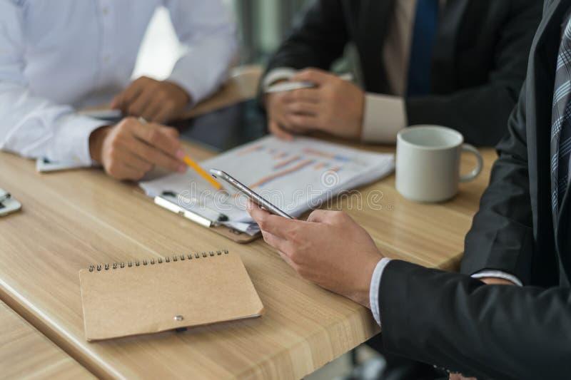 Affärsman som tre ser grafen i papper och samtal om affärsplan, marknadsföring och finansiellt i framtiden royaltyfri bild