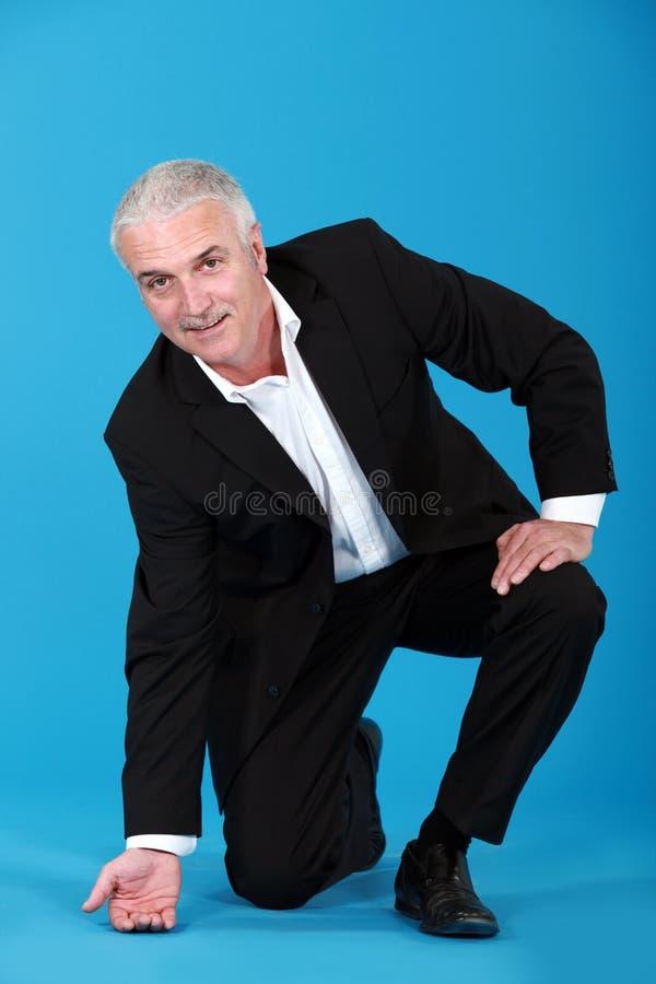 Affärsman som trycker på golvet royaltyfri fotografi