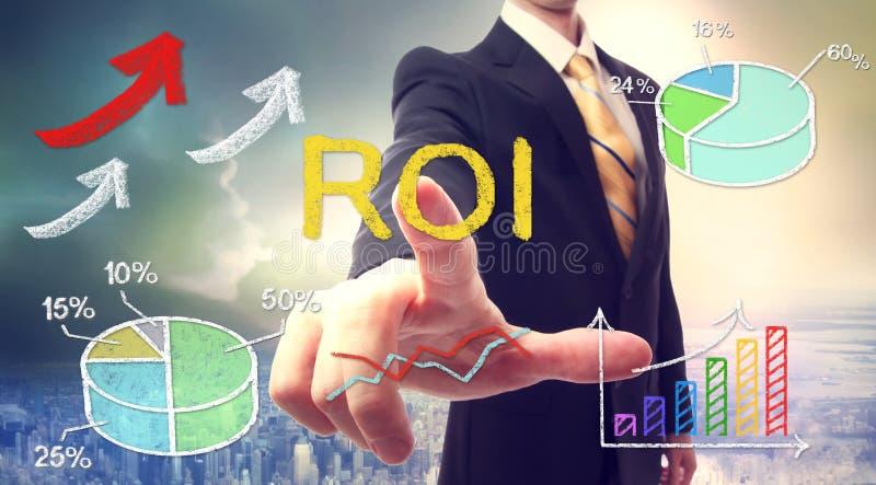 Affärsman som trycker på ROI (retur på investering) royaltyfria foton