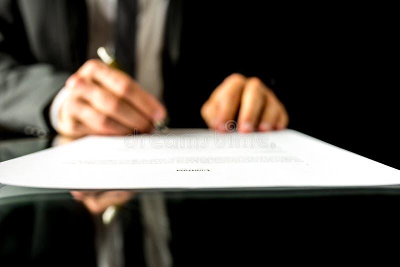 Affärsman som undertecknar ett dokument med fokusen till textavtalet arkivfoto