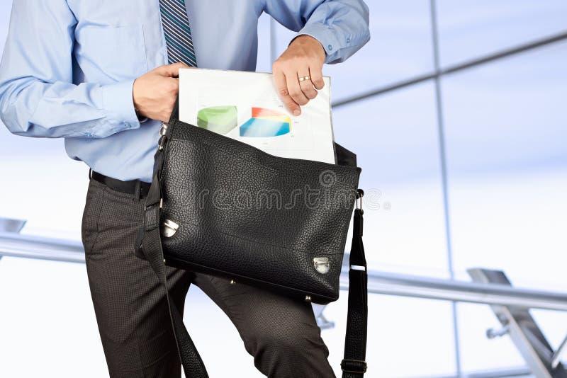 Affärsman som ut rymmer och får dokument med grafer från arkivbild