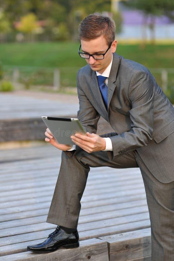 Affärsman som utanför använder den elektroniska minnestavlan fotografering för bildbyråer
