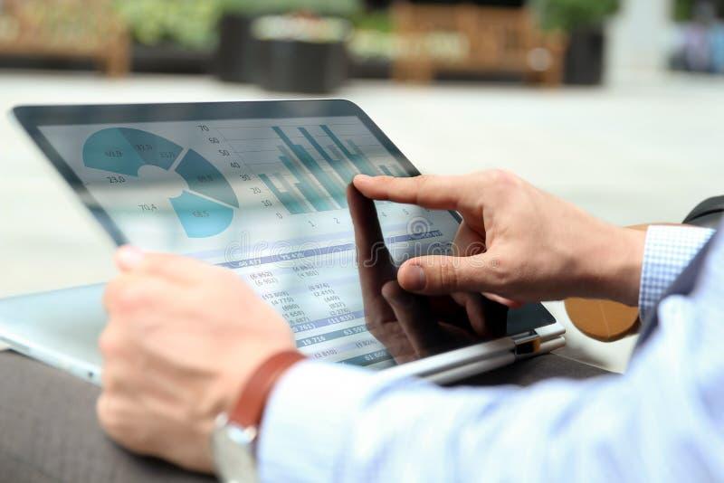 Affärsman som utanför arbetar och analyserar finansiella diagram på grafer på en bärbar dator arkivbilder