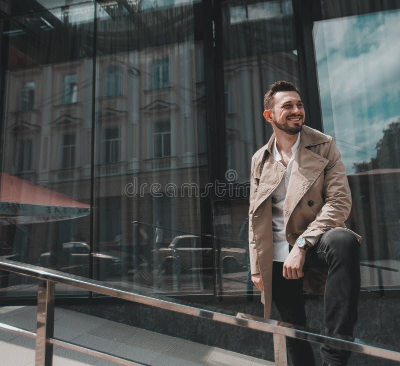 Affärsman som utanför går nära stor kontorsbyggnad och omkring ser arkivfoton