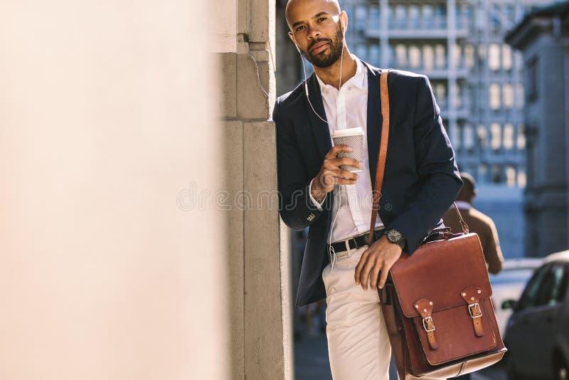 Affärsman som utomhus lutar till väggen med kaffe arkivfoton