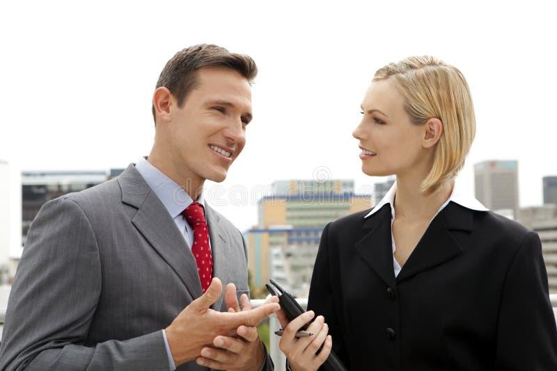 Affärsman som utomhus talar till affärskvinnan royaltyfri bild