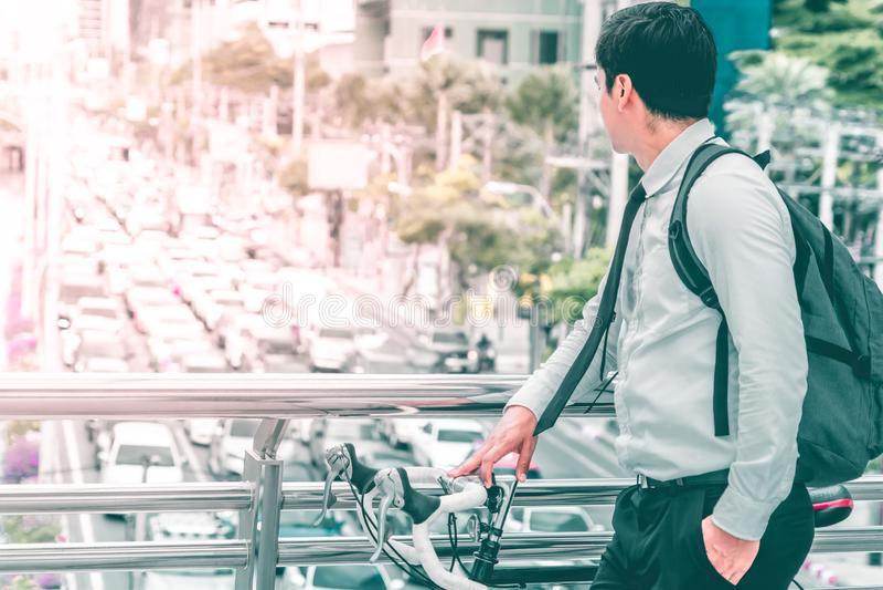 Affärsman som väljer att rida cykeln för att arbeta för att undvika Bangkok trafikstockning royaltyfri fotografi