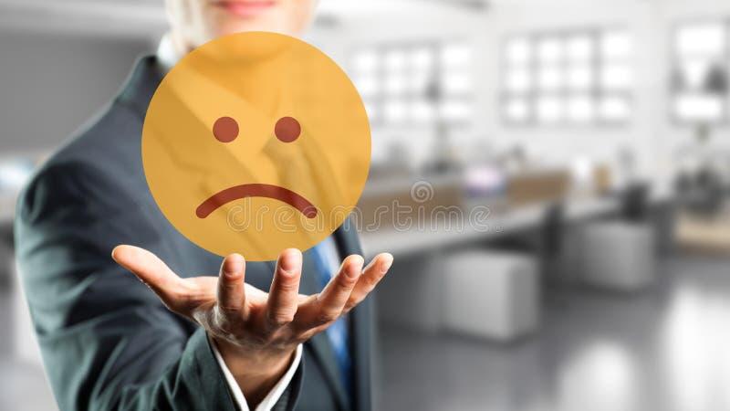 Affärsman som väljer en ledsen lynneemoticon arkivfoto