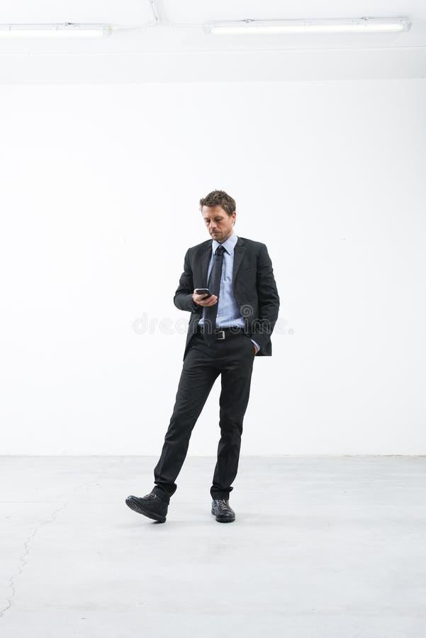 Affärsman som väntar med mobiltelefonen royaltyfria foton