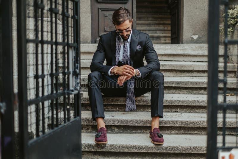 Affärsman som väntar på trappan och på den tiden ser arkivbild