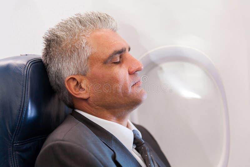 Affärsman som vilar flygplanet arkivbild