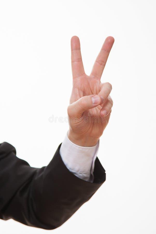 Affärsman som visar ett tecken av segern arkivfoto