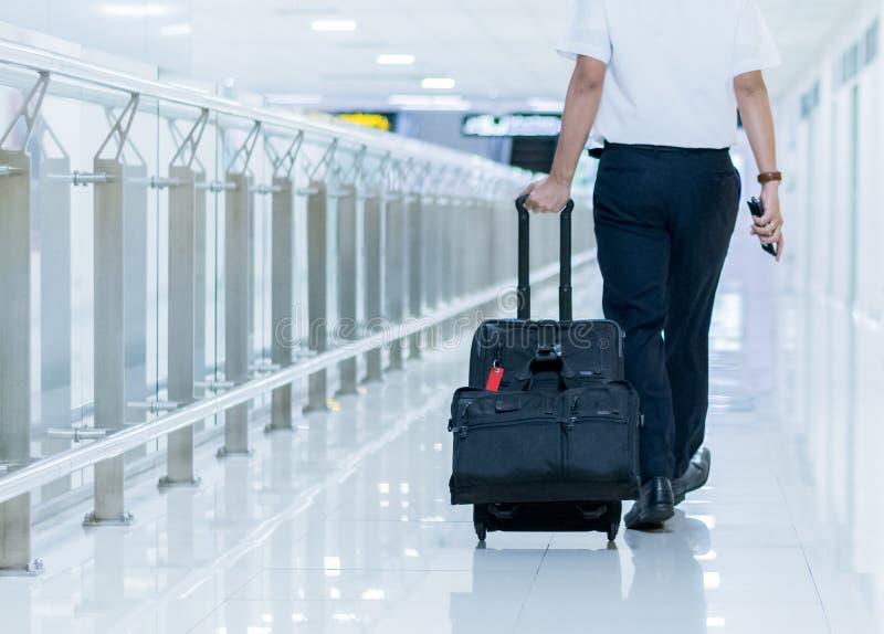 Affärsman som wolking på gångbanan i flygplats Gående abro för affärsman royaltyfria bilder