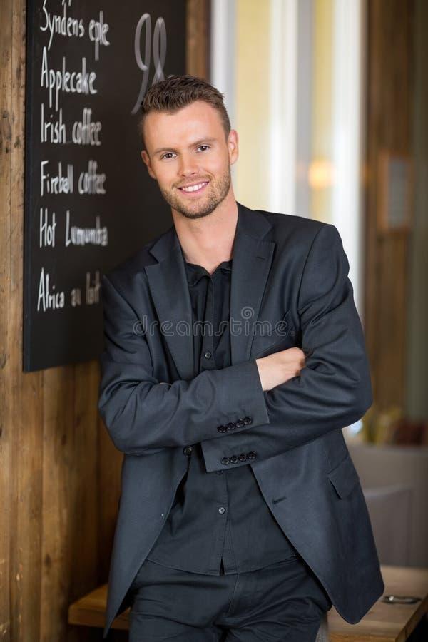 Affärsman Standing Arms Crossed i Coffeeshop royaltyfria foton