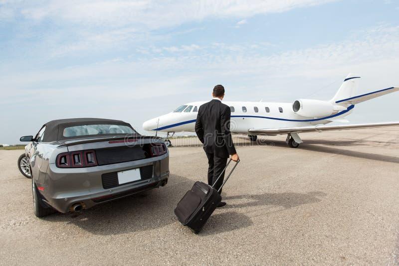 Affärsman Standing By Car och privata Jet At royaltyfri fotografi