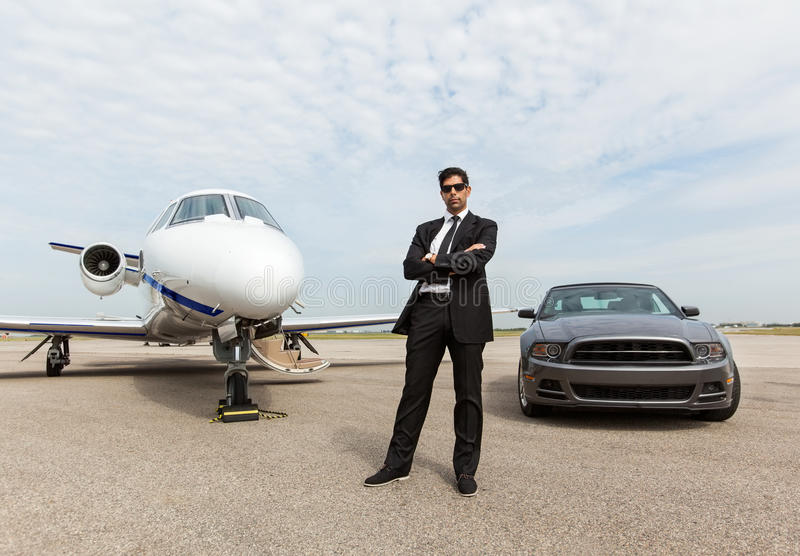 Affärsman Standing By Car och privata Jet At royaltyfri foto