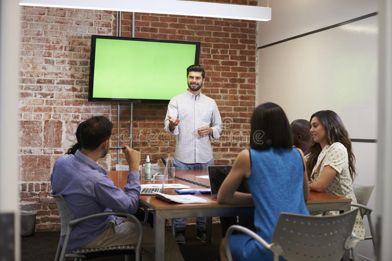 Affärsman Standing By Screen som levererar presentation arkivfoton