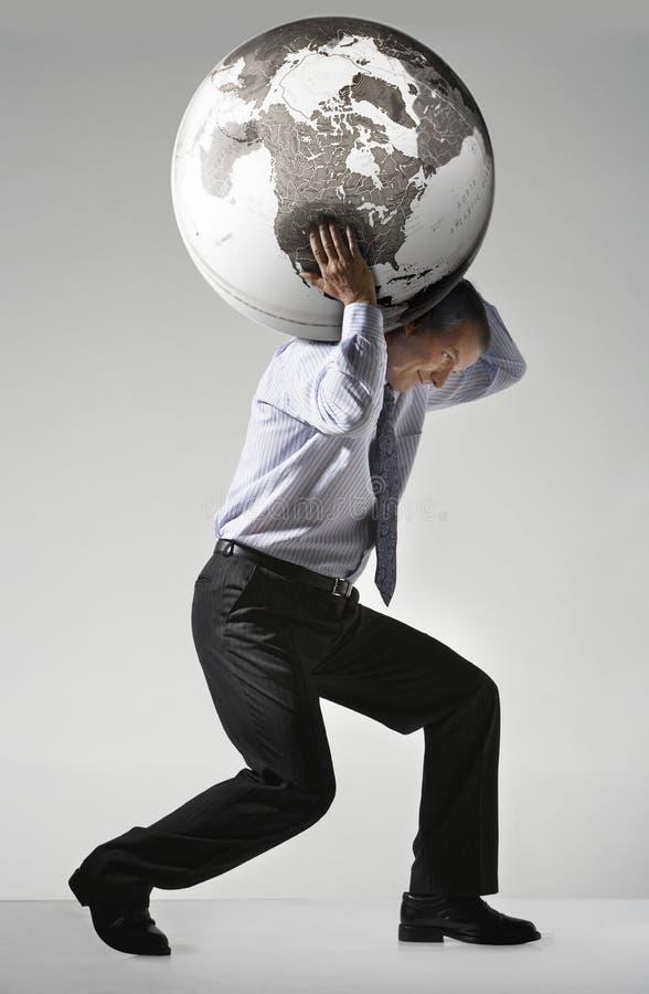 Affärsman Struggling To Carry Globe On Shoulders royaltyfri foto