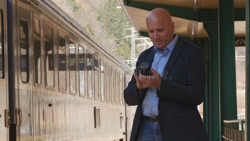 Affärsman Talking till mobiltelefonen i en drevstation royaltyfria foton