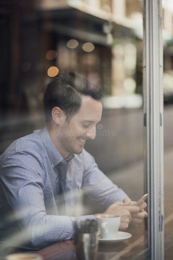 Affärsman Texting In Cafe arkivbild
