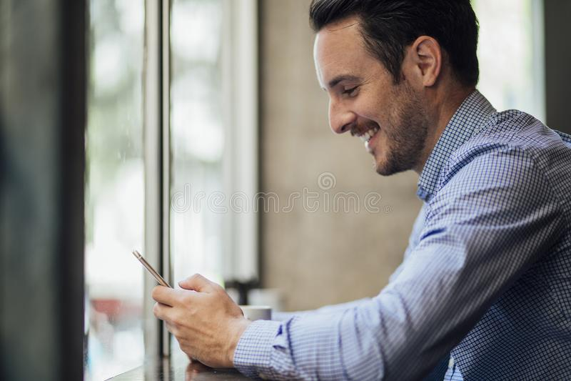 Affärsman Texting In Cafe royaltyfri bild