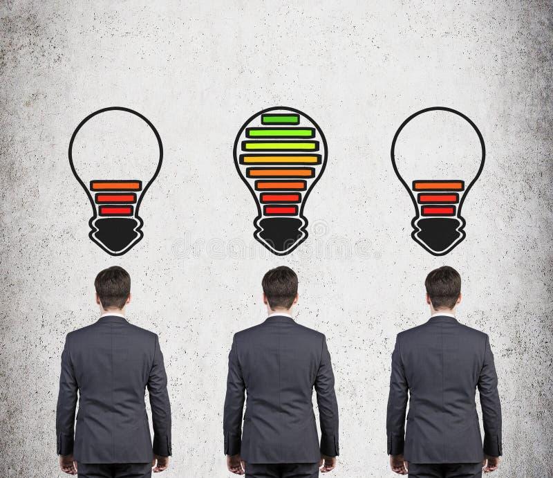 Affärsman tre med lampbatteriet royaltyfri foto