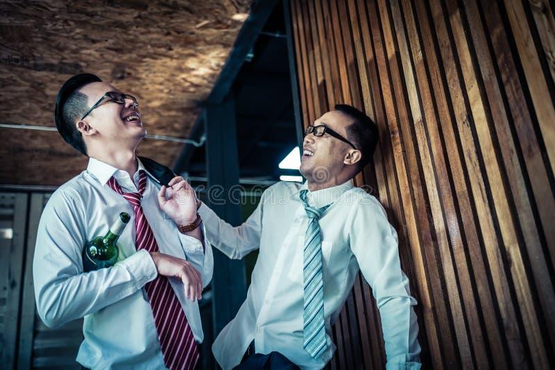 Affärsman två är drucken och skratta, når han har druckit hårt i restaurang som firar framgången av arbete arkivfoton