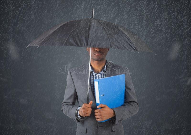 Affärsman under paraplyet mot i regn mot grå bakgrund royaltyfri bild